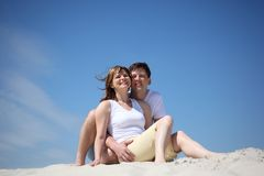 Couple in white shirts sitting on sand Royalty Free Stock Photo