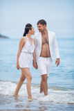 Couple in white walking along waters edge and talking Stock Photography