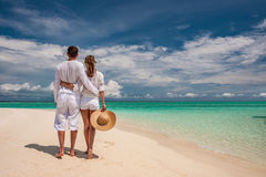 Couple in white walking on a beach at Maldives Royalty Free Stock Images
