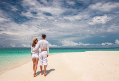 Couple in white walking on a beach at Maldives Royalty Free Stock Image