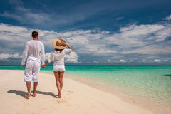 Couple in white walking on a beach at Maldives Royalty Free Stock Photography