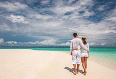 Couple in white walking on a beach at Maldives Stock Images