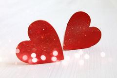 Couple of white wooden hearts. Glitter overlay Royalty Free Stock Photo