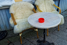 Couple of wicker chairs covered with sheepskin Stock Photo
