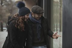 Couple window shopping outdoors in winter stock photo
