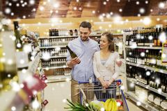 Couple with wine and shopping cart at liquor store Stock Photos