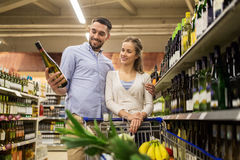 Couple with wine and shopping cart at liquor store Stock Image