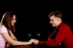 Couple with wine by a table. Royalty Free Stock Images