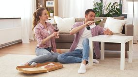 Couple with wine and takeaway pizza at home