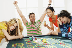 Couple Winning While Friends Lose On Roulette Table Stock Image