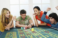 Couple Winning While Friends Lose On Roulette Table Royalty Free Stock Images