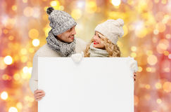 Couple in winter clothes with blank white board Royalty Free Stock Photos