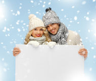 Couple in a winter clothes holding blank board Royalty Free Stock Photos
