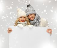 Couple in a winter clothes holding blank board Stock Image