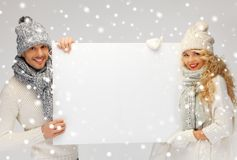 Couple in a winter clothes holding blank board Stock Images