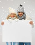 Couple in a winter clothes holding blank board Royalty Free Stock Images
