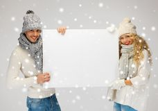 Couple in a winter clothes holding blank board Royalty Free Stock Image
