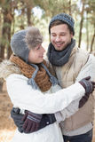 Couple in winter clothing embracing in the woods Stock Photography