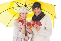 Couple in winter fashion showing autumn leaves under umbrella Royalty Free Stock Images