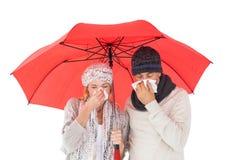 Couple in winter fashion sneezing under umbrella Stock Images