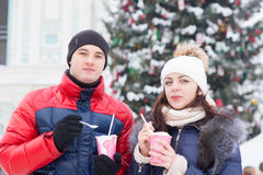 Couple in Winter Outfits Holding with Milkshake Stock Image