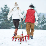 Couple in winter pulling a sled Stock Images