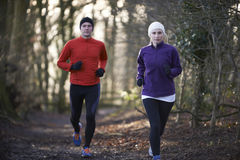 Couple On Winter Run Through Woodland Stock Photo