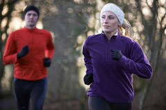 Couple On Winter Run Through Woodland Royalty Free Stock Images