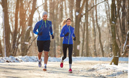 Couple in winter running together in nature Royalty Free Stock Photos