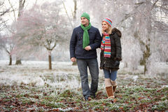 Couple On Winter Walk Through Frosty Landscape Stock Images