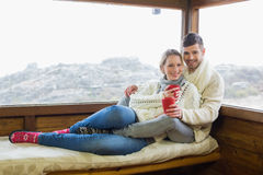 Couple in winter wear with coffee cups against cabin window Stock Photography