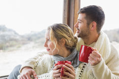 Couple in winter wear with cups looking out through window Stock Photos