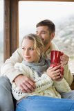Couple in winter wear with cups looking out through window Royalty Free Stock Photo