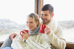 Couple in winter wear drinking coffee against window Royalty Free Stock Image