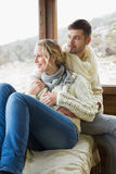 Couple in winter wear looking out through cabin window Royalty Free Stock Image