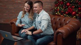 Young couple chatting with relatives via webcam stock video footage