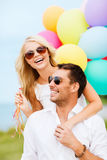 Couple With Colorful Balloons At Seaside Stock Image