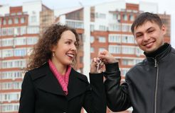 Couple With Key Against Many-storeyed House Royalty Free Stock Image