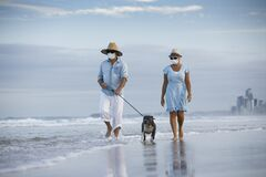 Free Couple With Medical Masks Splash Eachother While Walking A Dog By The Seaside Royalty Free Stock Photos - 177393178