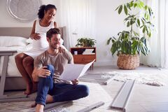 Free Couple With Pregnant Woman Putting Together Self Assembly Baby Cot In Bedroom Stock Image - 196331051