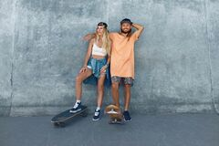 Free Couple With Skateboards Portrait. Guy And Girl In Casual Outfit Against Concrete Wall At Skatepark Royalty Free Stock Photography - 197110797