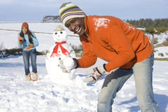 Free Couple With Snowman In Snowy Field Royalty Free Stock Images - 41715929