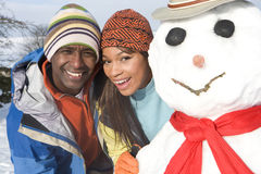 Free Couple With Snowman In Snowy Field Stock Images - 41718244