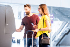 Couple withdrawing money at the airport royalty free stock image