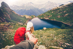 Couple Woman with backpack holding Man hand. Following Travel hiking Lifestyle concept lake and mountains landscape on background Stock Photography