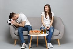 Couple woman boring man football fans in white t-shirt cheer up support favorite team with soccer ball, sitting isolated. Couple women boring men football fans stock images