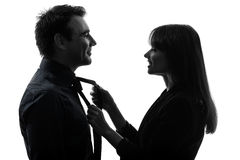 Couple woman helping man tying silhouette Stock Images