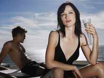 Couple With Woman Holding Champagne Glass By Sea Royalty Free Stock Photos