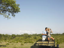 Couple With Woman Looking Through Binoculars In Jeep  Royalty Free Stock Photo