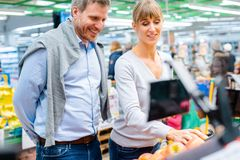 Couple of woman and man buying fresh fruit in supermarket. Cheerful couple of women and men buying fresh fruit in supermarket royalty free stock photography